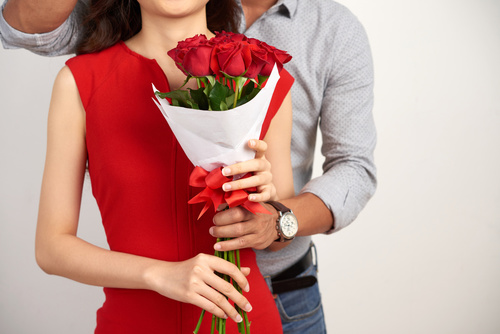 Cropped image of boyfriend presenting bouquet of flowers