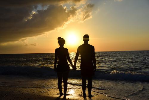 giovane coppia che si tiene per mano in spiaggia durante il tram