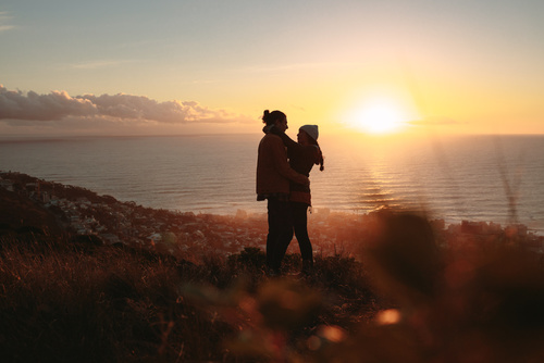 Romantic couple embracing on mountain top at sunset