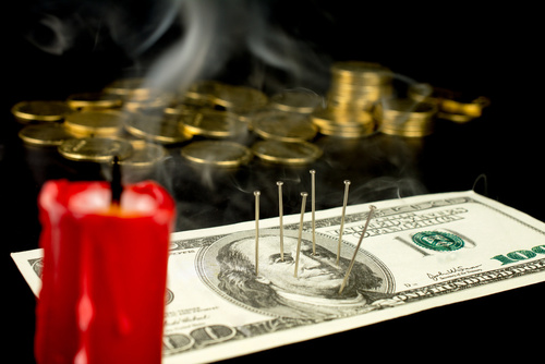 needles stuck in a dollar bill voodoo ritual, red candle, smoke